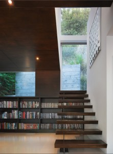 Ebony-stained oak bookshelves and wall and ceiling paneling contrast with the white epoxy resin floor in the library area of a Hollywood Hills residence renovated by Griffin Enright Architects. Photograph by Benny Chan, Fotoworks