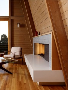 Unstained white oak flooring and alder plank walls create a warm cocoon around the fireplace in an Oakland, California living room renovated by Burton Architecture. Photograph by Cesar Rubio