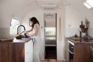 The galley kitchen in a 1977Airstream Overlander renovated by The Modern Caravan features custom walnut counters and cabinetry. Photograph by Kate Oliver