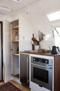 Built-in kitchen appliances include a 3.3-cubic-foot built-in refrigerator, a convection oven—both in stainless steel—and a dual-burner induction cooktop. Photograph by Kate Oliver