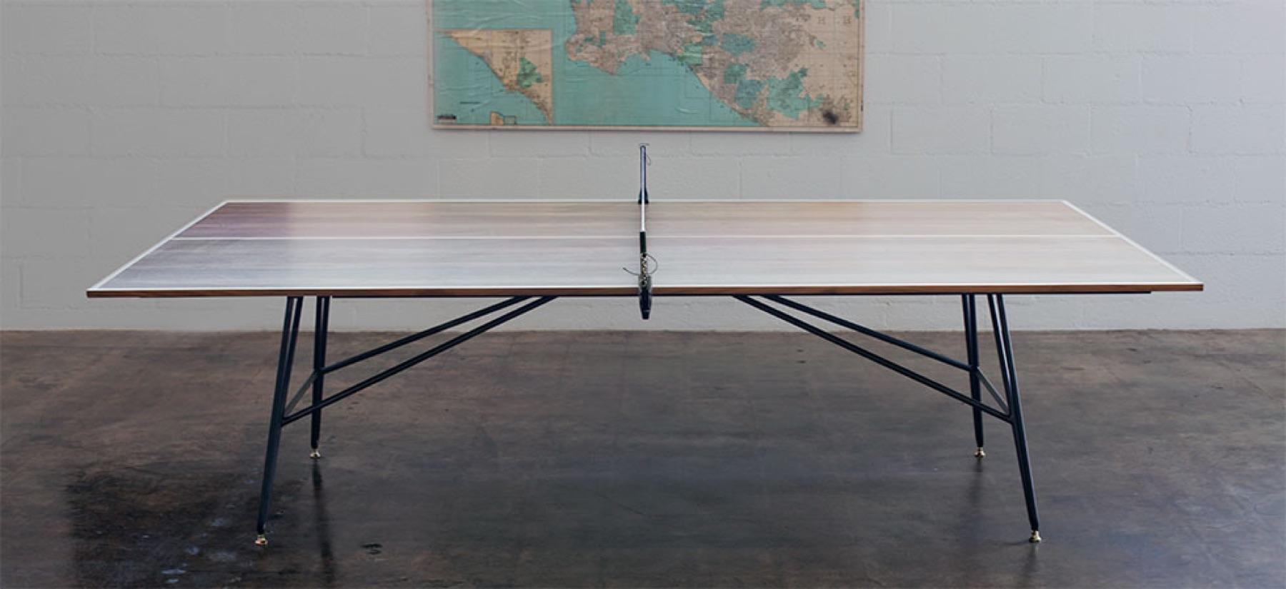 The Clip Leg Ping Pong Table from District Mills has a reclaimed walnut top on black steel and brass legs.