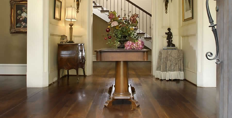 Wide-plank walnut flooring by Carlise makes a lustrous statement in a tradional entry hall.